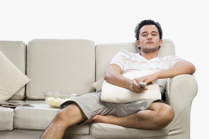 A Man Sitting On A Sofa Watching The Tv