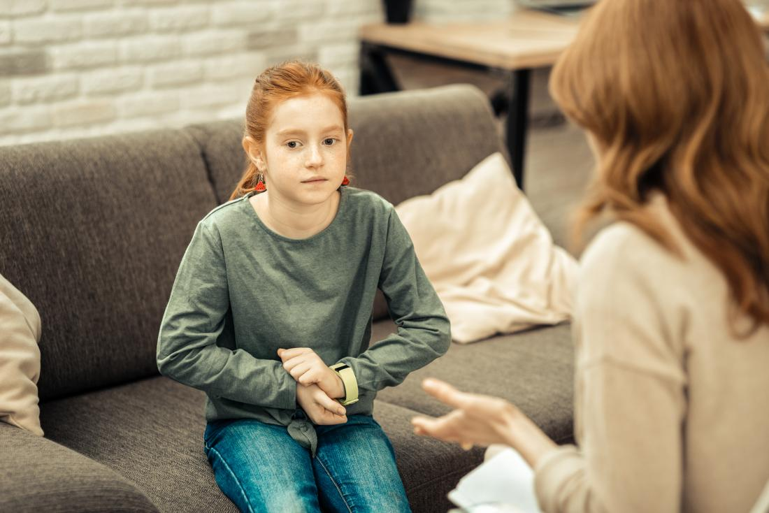 Child with autism in therapy speaking with adult or parent, avoiding eye contact and looking anxious