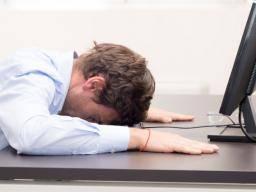 a hungover man is slumped at his desk - DIARREE NA HET DRINKEN VAN ALCOHOL: BIER WIJN STERKE DRANK WAT IS DE OORZAAK