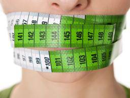 woman with tape measure around her mouth - Alles wat u moet weten over vasten met water