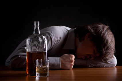 drunk man lying on the table with whiskey glass