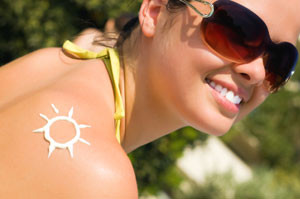 Photograph of lady with sun cream on shoulder in shape of sun