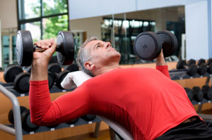 Man exercising with dumbbells at gym