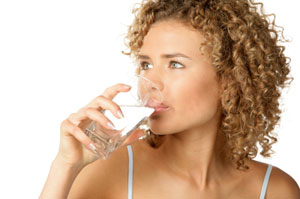 A lady drinks a glass of water