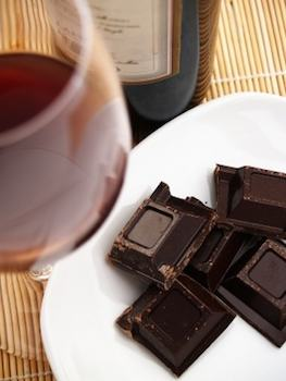 Squares of chocolate next to a glass of red wine.
