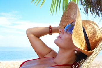 Lady resting on a tropical beach in the shade of a palm tree and wearing hat and sunglasses
