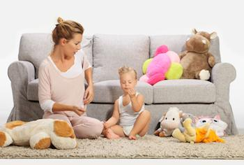Mother and child playing together on a rug in front of a sofa and a pile of soft toys.
