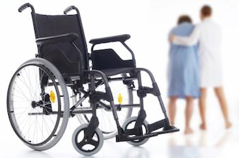 a patient being taken from a wheelchair by a doctor