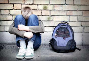 Boy sitting against a wall and hugging his knees