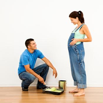 Pregnant lady and her partner preparing to paint the baby's bedroom yellow