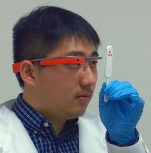 a doctor using Google Glass to take a picture of a medical test