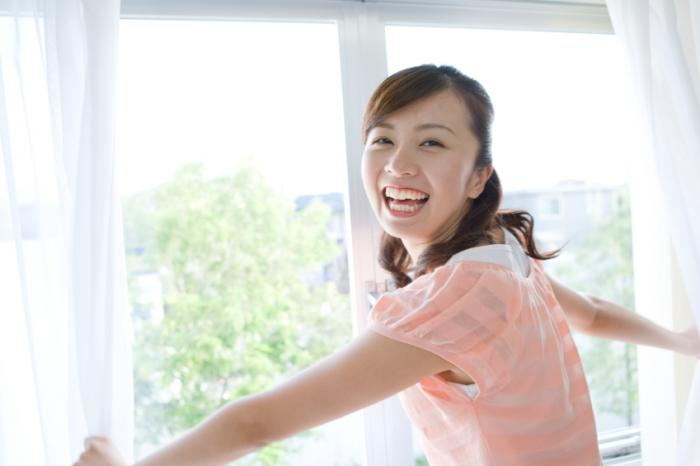 woman opening curtains to morning light