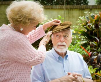 older lady helping an older man with putting on a hat