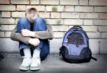 a depressed teenager hugging his knees