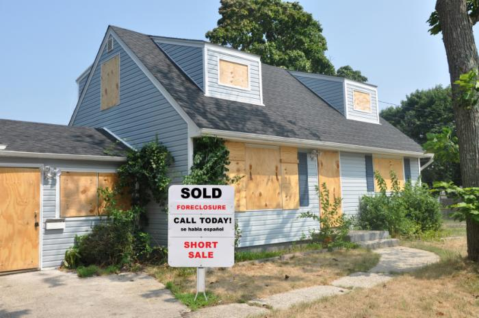 boarded up house with foreclosure sign