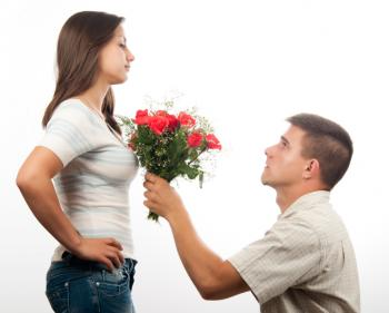 man kneeling and offering flowers to a woman