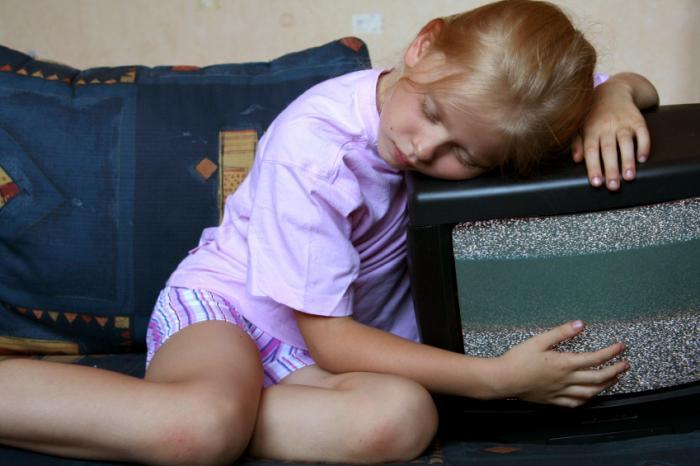 asleep child hugging a tv