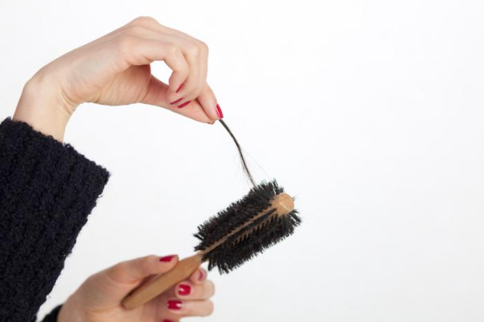 a hand picking a strand of hair from a hairbrush