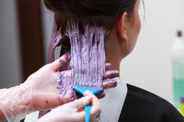 hairdresser coloring a woman's hair with dye