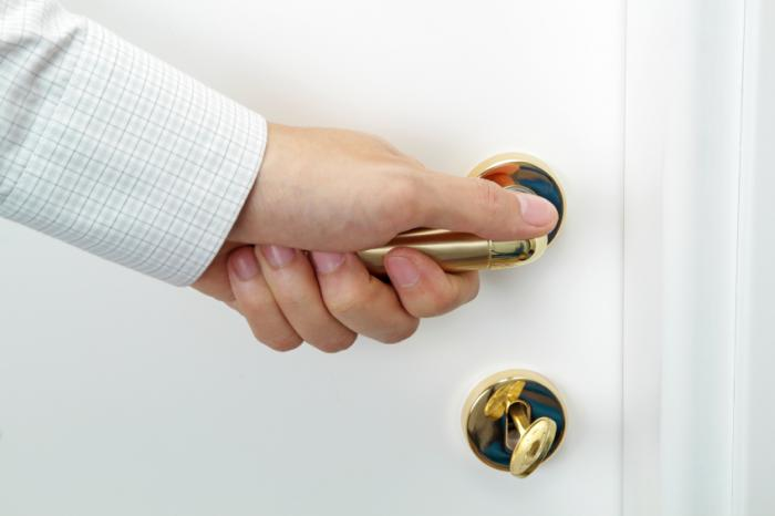hand on brass door handle