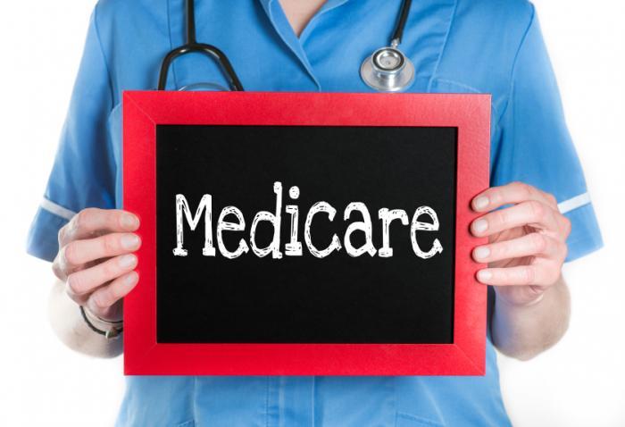 nurse holding medicare sign