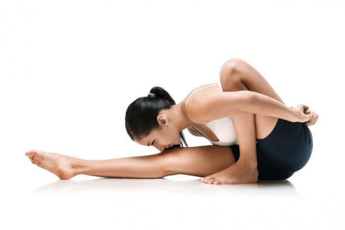 woman bending forward into yoga floor pose