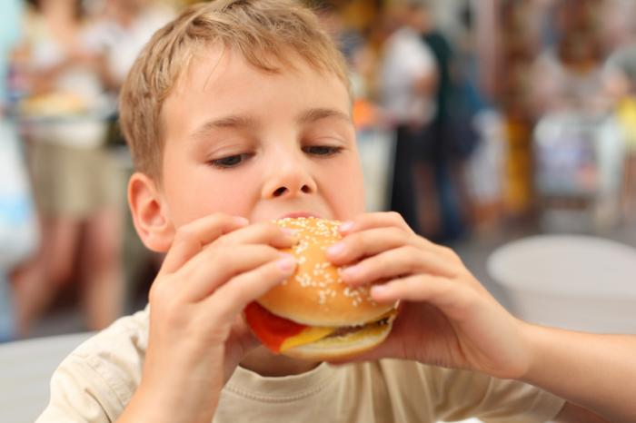 A young boy eating a burger