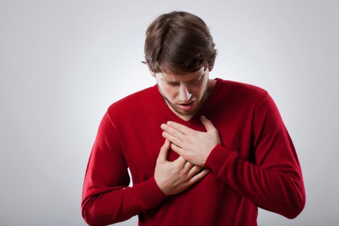 Man clutching chest in discomfort.