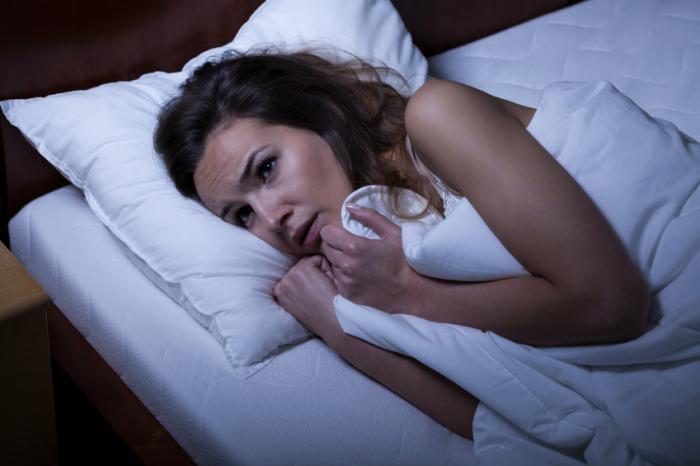 Worried woman lying in bed.