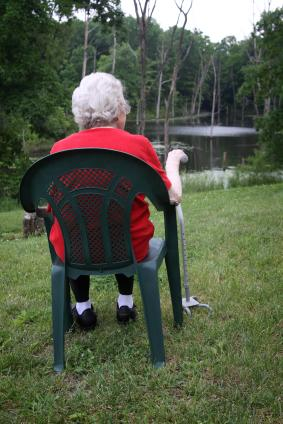 older lady with walking stick sitting by pond