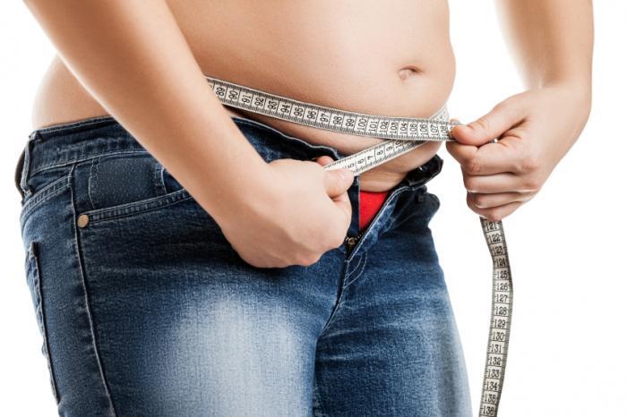 An overweight woman measuring waist