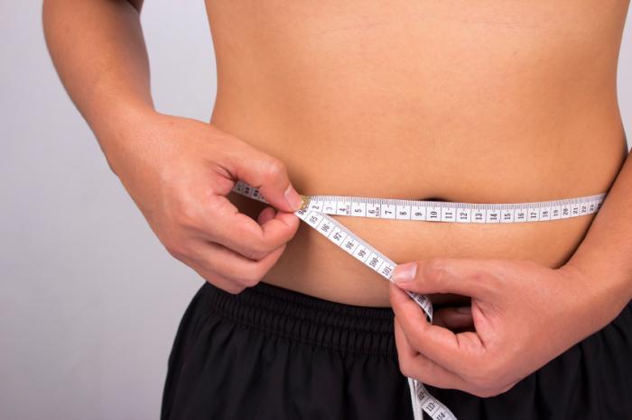Teen measuring belly.
