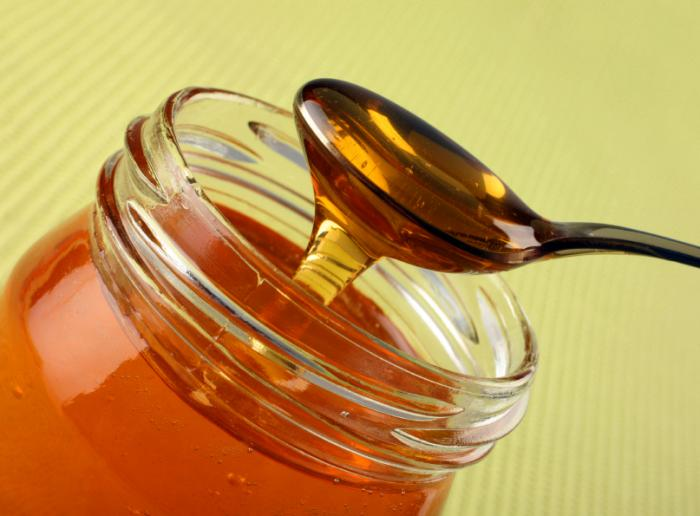 A spoonful of honey from a jar.