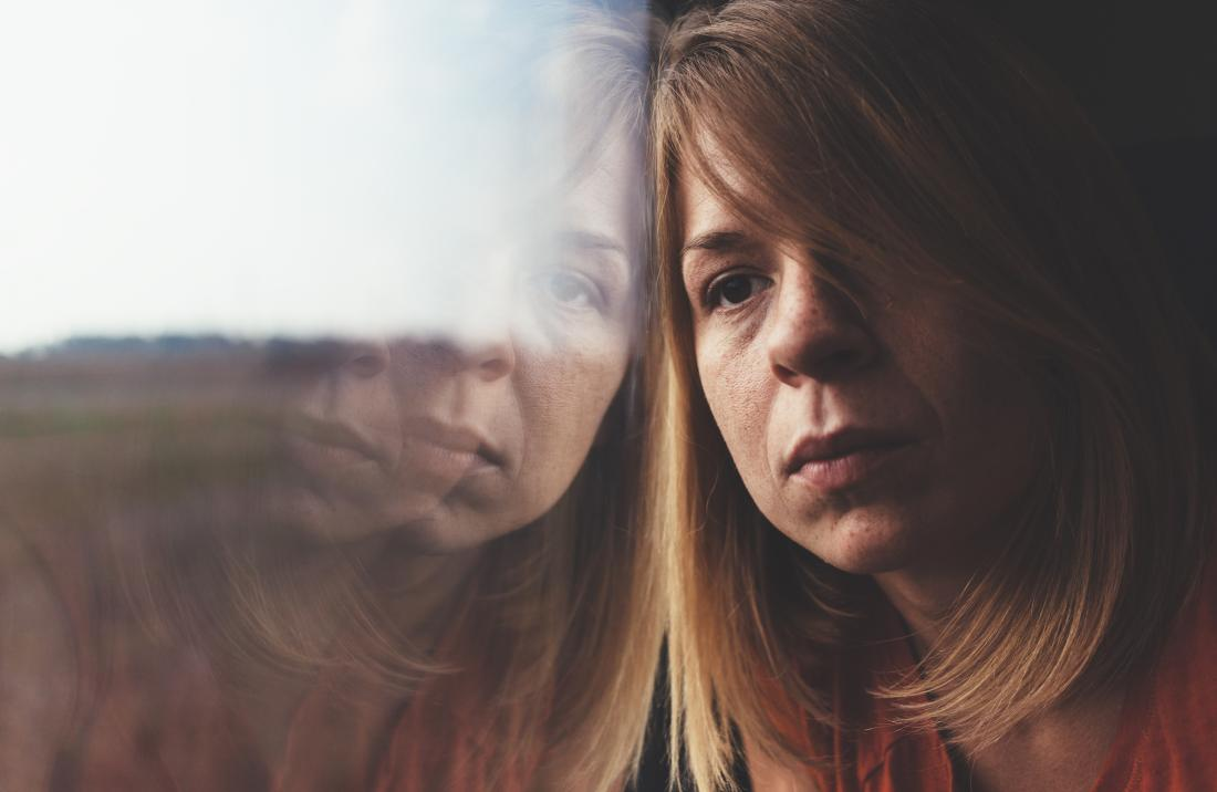 a sad woman looking out of a window